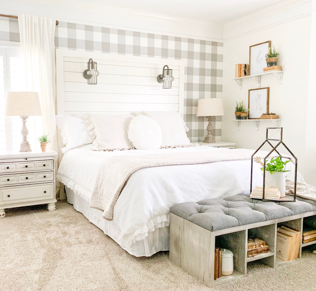 bedroom with large bed and bench and shelf decor of botanical prints