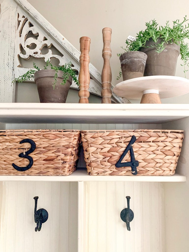 plant and candle decor on top of mudroom cubbies