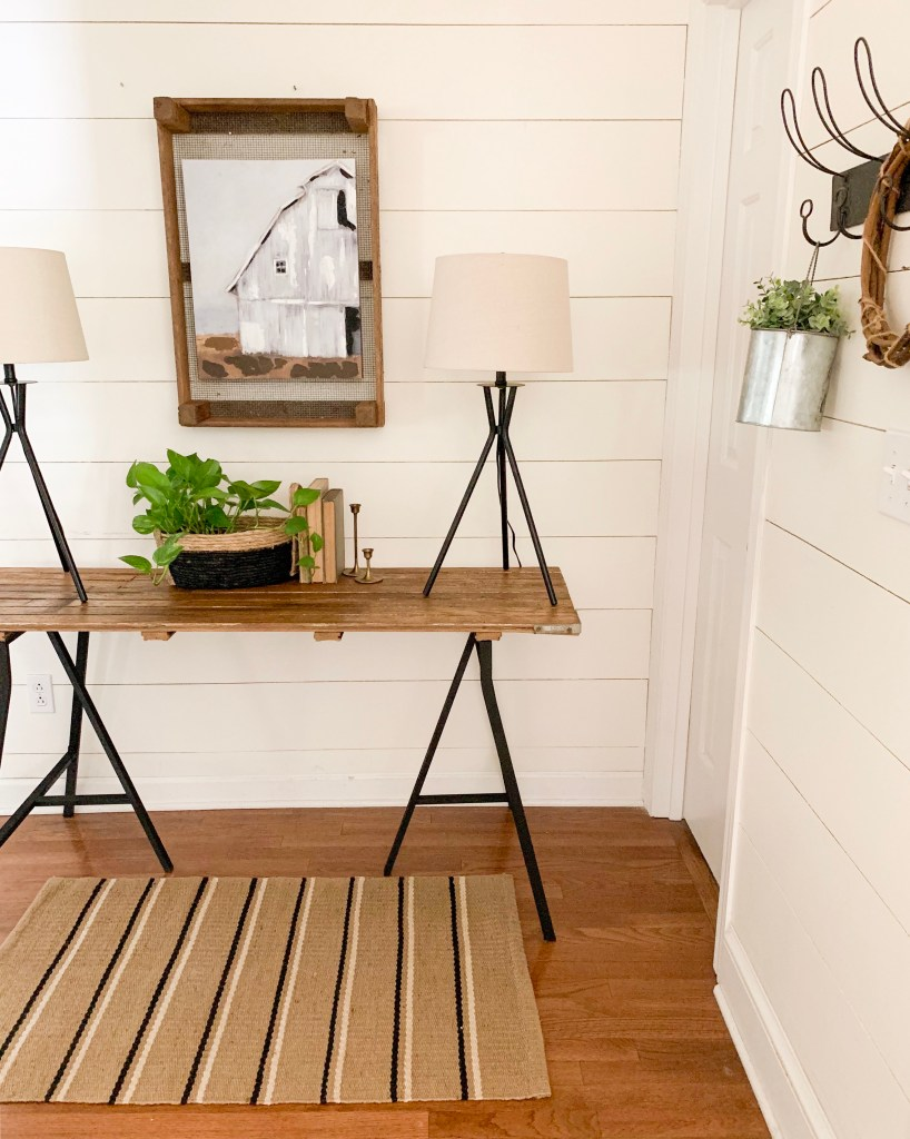 entryway table in front of shiplap wall